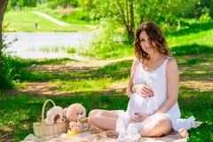 白色衣裳休息的怀孕的美丽的妇女 免版税图库摄影