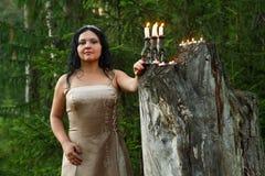 白色衣裳的一位森林神仙有烛台的点燃了在森林特写镜头的蜡烛 库存照片