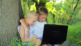 白色衣裳的两个男孩在公园坐 影视素材
