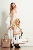 白色衣裳的两名妇女有袋子提包的 免版税库存图片