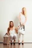 白色衣裳的两名妇女有袋子提包的 免版税图库摄影