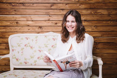 白色衣裳的女孩在与书的一条长凳 免版税图库摄影