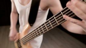 白色衣裳的年轻男性音乐家有在黑背景的米黄低音吉他的 低音吉他球员传神音乐 影视素材
