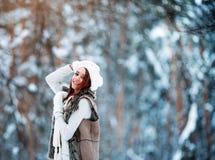 白色衣裳的美丽的女孩获得乐趣室外在冬天森林在雪花下 免版税库存照片