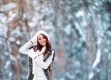 白色衣裳的美丽的女孩获得乐趣室外在冬天森林在雪花下 库存图片