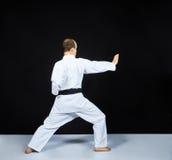 白色表面上,一位成人运动员训练一个块用他的手 库存照片