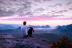 白色衬衣、黑暗的trousars和红色盖帽的成人运动员 姜短发人坐在谷上的锋利的峭壁在落矶山脉 库存照片