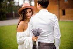 白色衬衣和卷曲新娘的新郎有淡紫色花束的白色礼服的  免版税库存照片