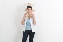 白色衬衣和牛仔裤的年轻微笑的妇女有运载长毛绒在她的肩膀的玩具猫的短发的 免版税库存图片