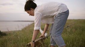 白色衬衣和牛仔裤的年轻深色的女孩在湖附近的meado 女孩准备一个画架运转 股票录像