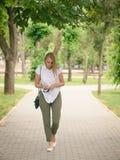 白色衬衣和绿色裤子的妇女有太阳镜的在手中步行沿着向下公园的胡同的 免版税库存图片