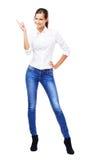 白色衬衣和蓝色牛仔裤的可爱的妇女指向copyspace的 免版税库存图片