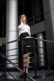 白色衬衣和黑裙子的年轻别致的企业女孩微笑 库存照片