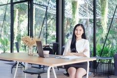 白色衬衣微笑的亚裔年轻美丽的女商人 免版税库存图片