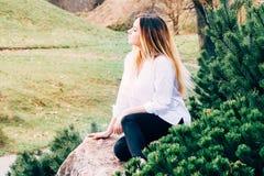 白色衬衣的一个相当年轻长发女孩在石头 免版税库存图片