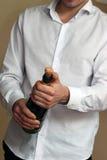白色衬衣的一位侍者打开一个瓶香宾 免版税图库摄影