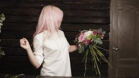 白色衬衣的专业卖花人装饰补全与完善的花的时兴的花束 股票录像