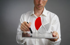 白色衬衣的人与在片剂计算机上的对预算计划的圆形统计图表,申请或财政统计一起使用 免版税库存图片