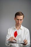 白色衬衣的人与在片剂计算机上的对预算计划的圆形统计图表,申请或财政统计一起使用 库存照片