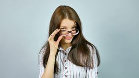 白色衬衣的可爱的女孩有看与兴趣的红色和蓝色条纹的照相机在她的镜片 股票视频
