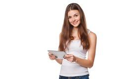 白色衬衣的可爱的微笑的女孩使用片剂 有片剂个人计算机的妇女,在白色背景 免版税库存照片
