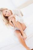 白色衬衣的可爱的年轻金发碧眼的女人微笑对照相机的坐床 免版税库存图片