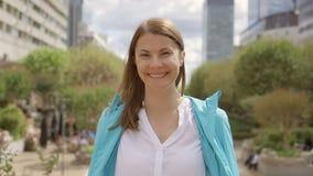 白色衬衣的女实业家在街市的城市 查看照相机 有专业的女性断裂 股票录像