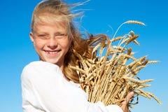 白色衬衣的孩子在手上的握麦子耳朵 免版税库存照片