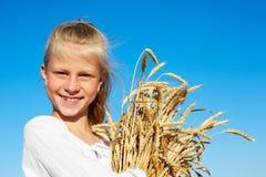 白色衬衣的孩子在手上的握麦子耳朵 库存照片