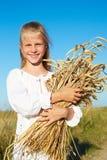 白色衬衣的孩子在手上的握麦子耳朵 免版税库存图片
