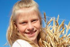 白色衬衣的孩子在手上的握麦子耳朵 图库摄影