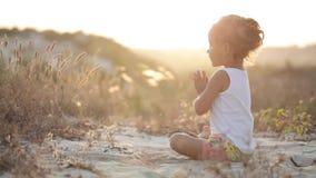白色衬衣的小逗人喜爱的女孩思考在日落坐沙子 影视素材