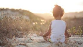 白色衬衣的小逗人喜爱的女孩思考在日落坐沙子 股票录像