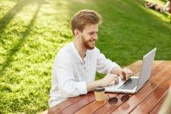 白色衬衣的微笑正面年轻红发不剃须的人,坐在美丽的公园,饮用的咖啡和写 库存图片
