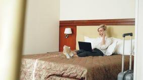 白色衬衣的微笑的女实业家使用在膝上型计算机和谈话在手机,当说谎在床上在旅馆客房时 影视素材