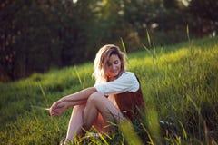 白色衬衣的愉快的妇女享受一顿野餐本质上的 女孩坐草,休息,放松 免版税图库摄影