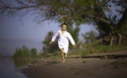 白色衬衣的愉快的男孩,运行沿河岸 免版税库存图片