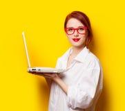 白色衬衣的愉快的红头发人女孩有计算机的 库存照片