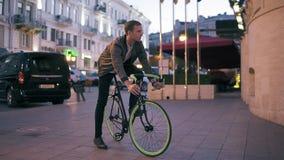 白色衬衣的愉快,微笑的年轻人和棕色皮夹克有一辆自行车在现代城市 为乘坐他的准备 股票视频