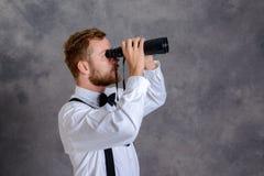 白色衬衣的有胡子的人和在灰色backgro前面的蝶形领结 免版税库存图片