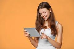 白色衬衣的激动的女孩使用片剂 有片剂个人计算机的微笑的妇女,隔绝在橙色背景 免版税库存图片
