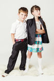 白色衬衣的男孩由肩膀拥抱一个女孩 免版税库存照片