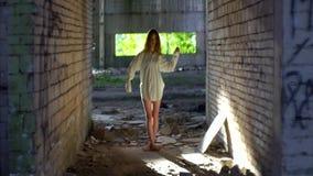 白色衬衣的神奇妇女奇怪地移动在老被破坏的大厦的手 股票录像