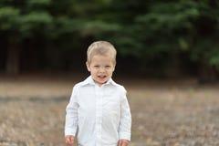白色衬衣的逗人喜爱的愉快的小孩 免版税图库摄影