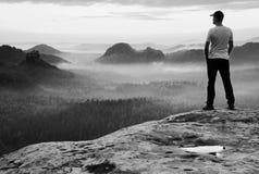 白色衬衣的高人和有红色棒球帽的黑长裤在急剧峭壁和手表停留对谷 五颜六色的有薄雾的mornin 免版税库存图片