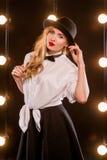 白色衬衣的,黑帽会议年轻白肤金发的可爱的妇女 免版税库存照片
