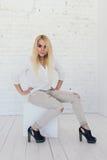 白色衬衣的年轻性感的白肤金发的妇女和牛仔裤和黑鞋子 免版税库存照片