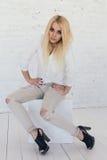 白色衬衣的年轻性感的白肤金发的妇女和牛仔裤和黑鞋子 库存照片