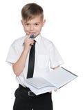 白色衬衣的年轻男孩有笔记本的 免版税库存照片
