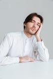白色衬衣的Hadsome年轻人睡觉在书桌的 免版税库存照片